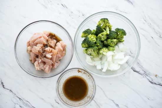 Chicken in one bowl, broccoli and onions in another, marinade in a third