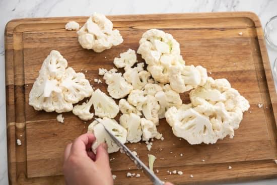 Cauliflower being cut on a board
