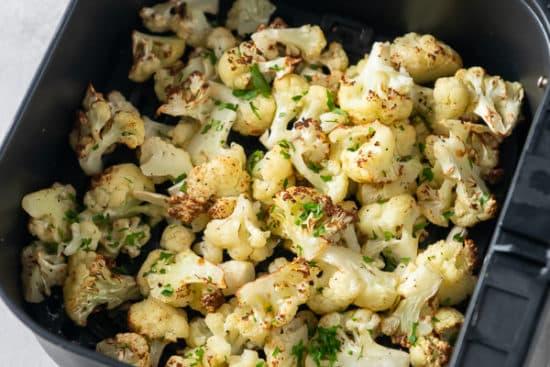 Cooked cauliflower in an air fryer basket