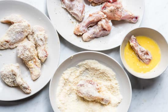 Coating chicken wings in egg and parmesan